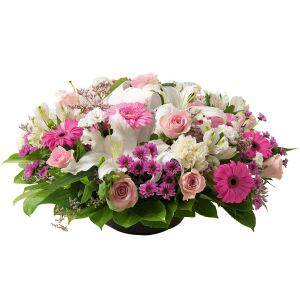 Round funeral arrangement of mixed flowers in white and pink tones